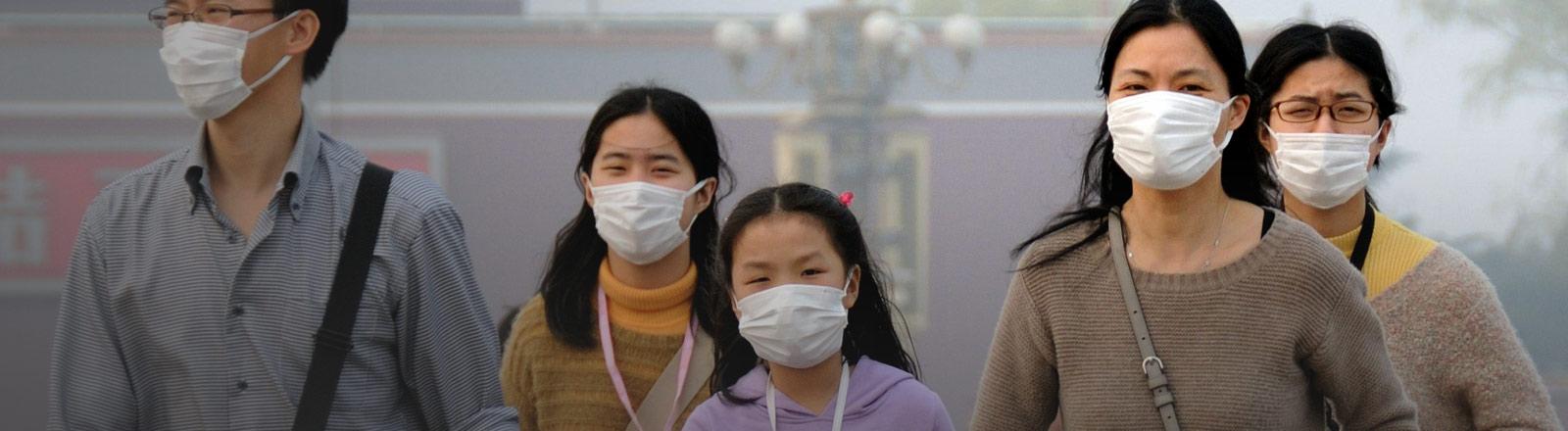 Eine Familie in Asien geht auf der Straße mit Mundschutz.