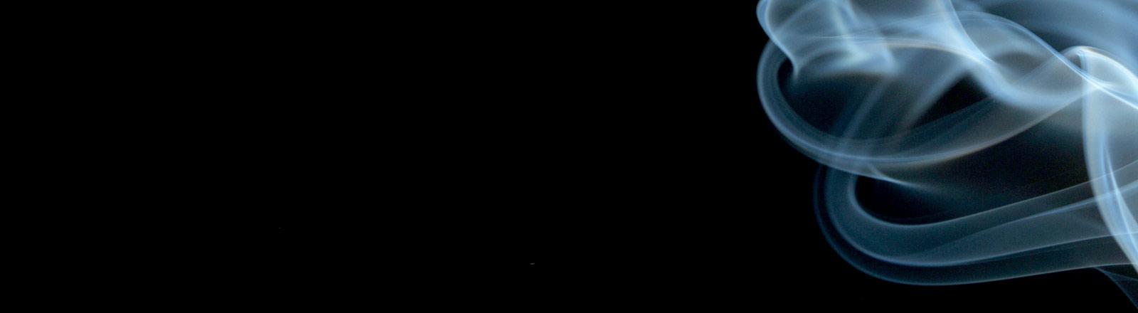 Zigarettenrauch vor schwarzem Hintergrund.