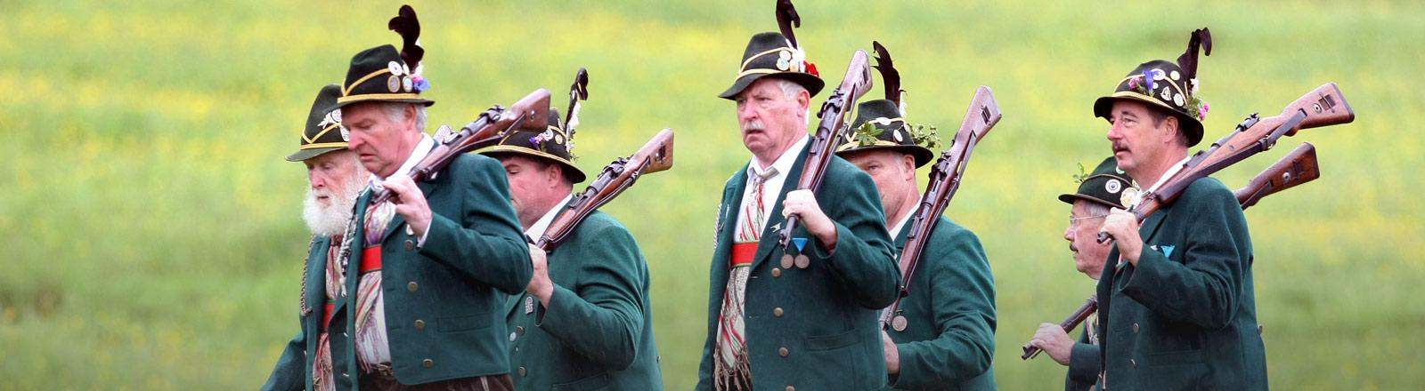 Mehrere Mitglieder eines Schützenvereins in grünen Trachten mit ihren Gewehren.