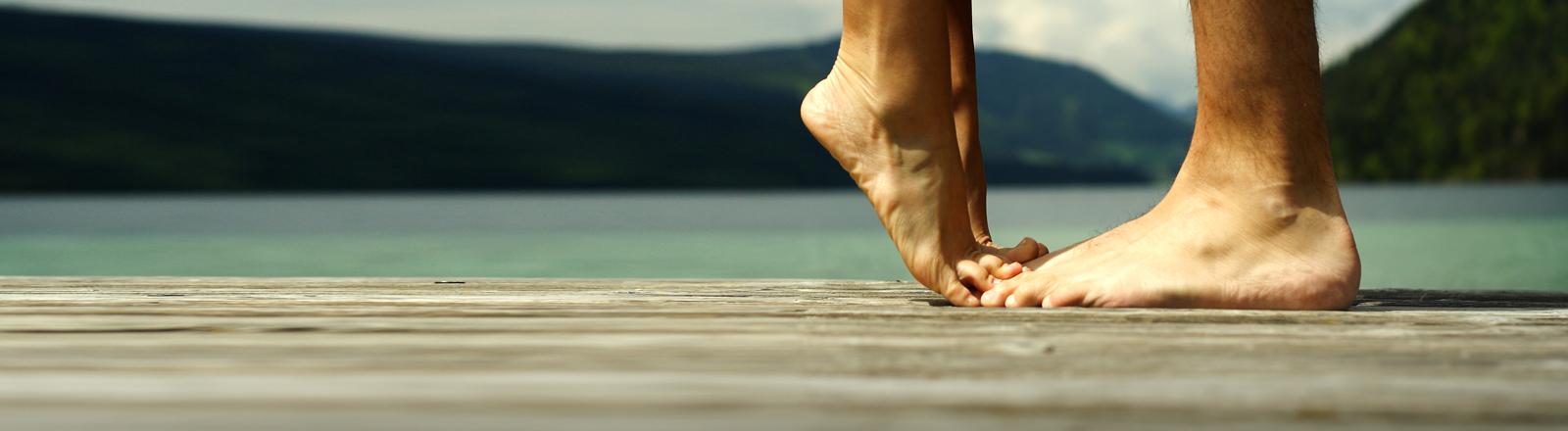 Ein Paar Füße auf einem Steg. Eins steht auf Zehenspitzen.