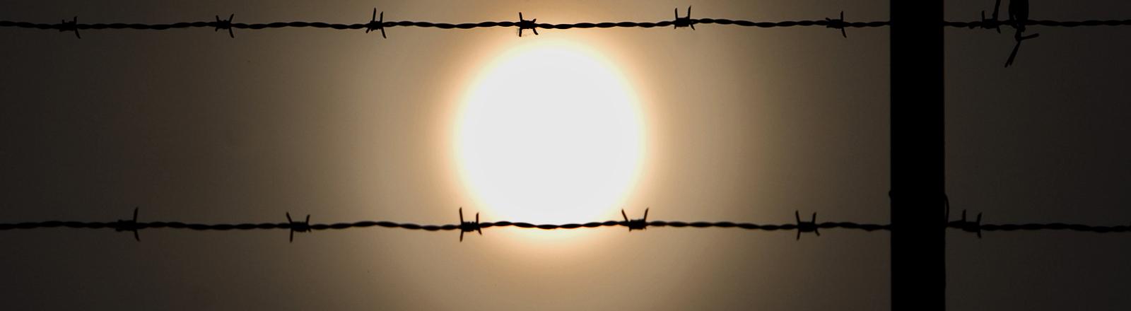 Ein Stacheldrahtzaun vor der Sonne
