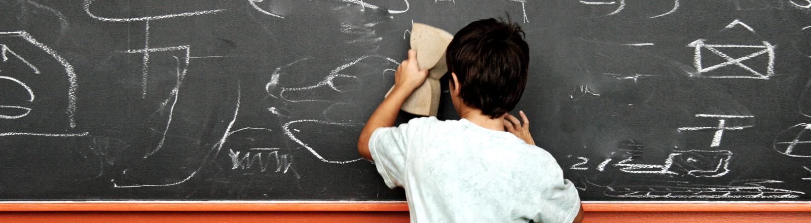 Ein Junge wischt eine Schultafel.