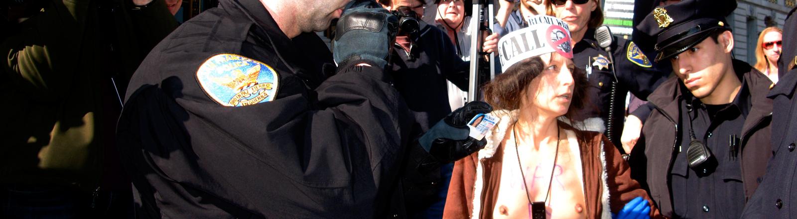 Eine nackte Demonstrantin ist umringt von Polizisten.