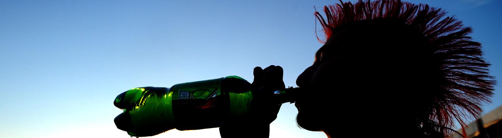 Ein Mann mit Irokese trinkt aus einer Flasche.
