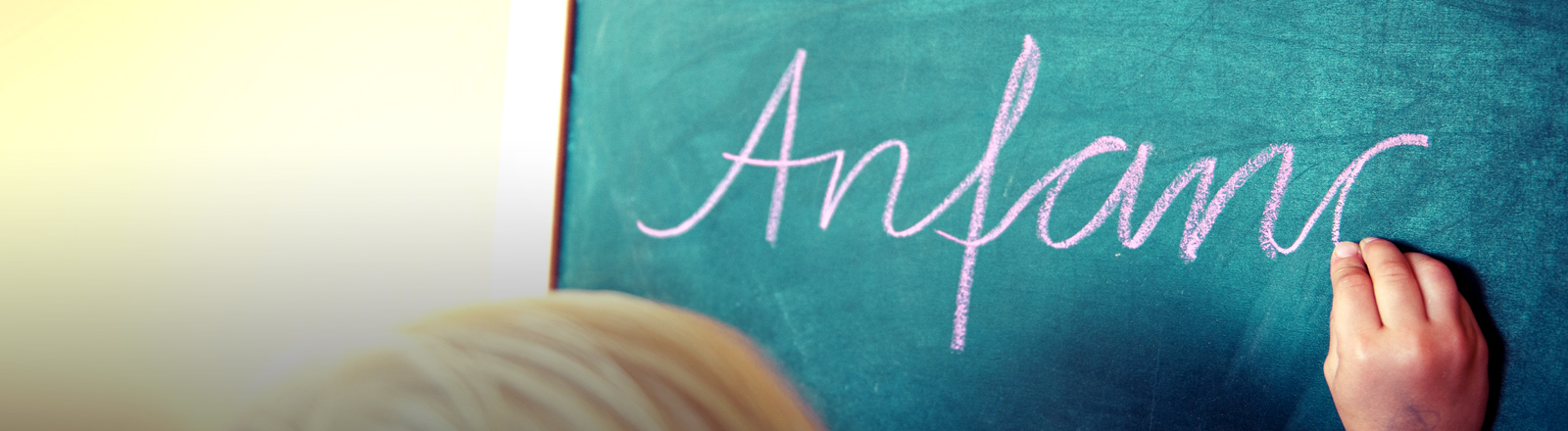 """Ein Kind schreibt das Wort """"Anfang"""" an die Tafel."""