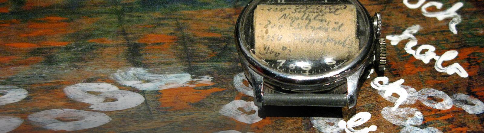 Ein Pfuschzettel in einer Uhr.