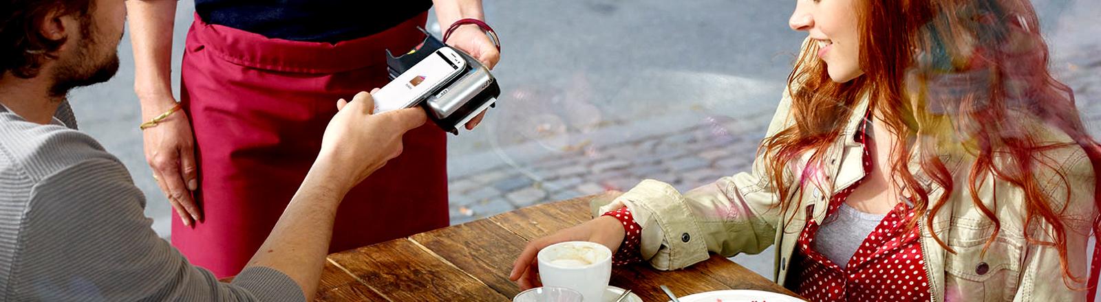 Ein Mann bezahlt in einem Café mit seinem Smartphone.