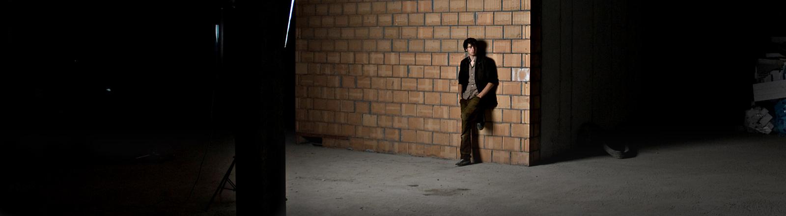 Ein Mann lehnt in einer dunklen Ecke an einer Hauswand.
