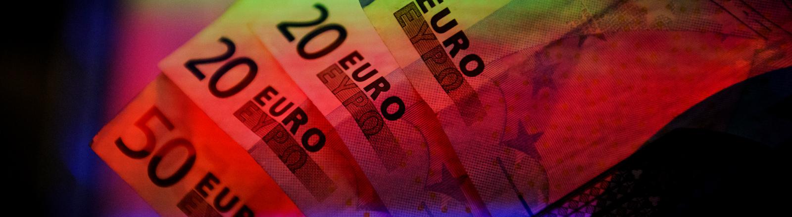 Vier Euroscheine in rotem und grünem Licht.