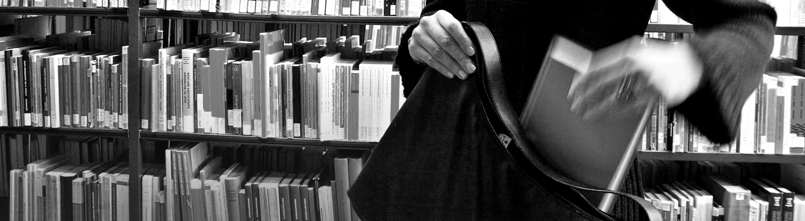 Eine Frau steckt in einer Bibliothek ein Buch in ihre Tasche.