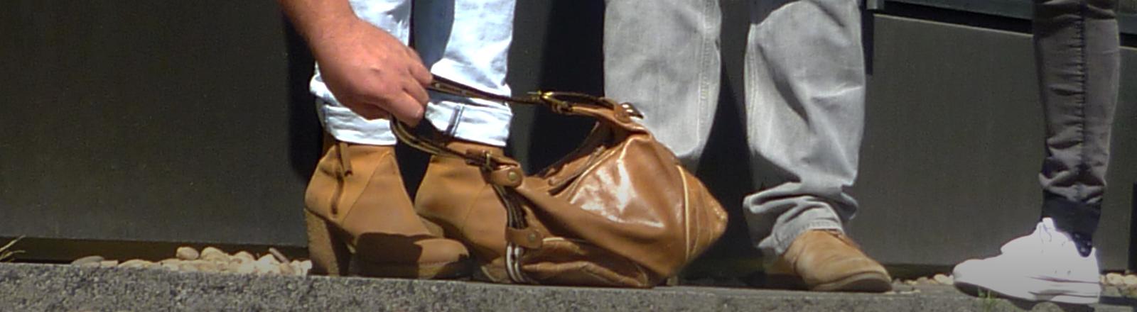 Jemand entwendet eine Handtasche.