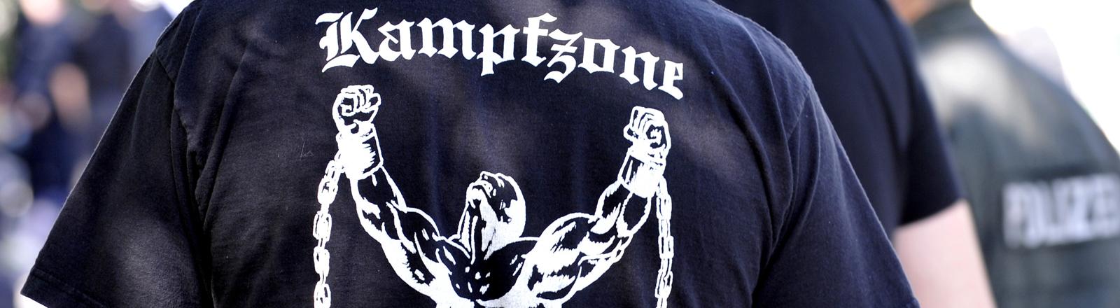 """Rücken eines Neonazis in Dortmund. Auf seinem T-Shirt steht """"Kampfzone"""""""