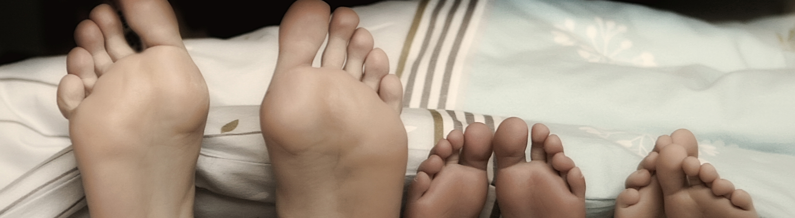 Ein Paar Erwachsene Füße und zwei Paar Kinderfüße, die unter einer Bettdecke hervorschauen