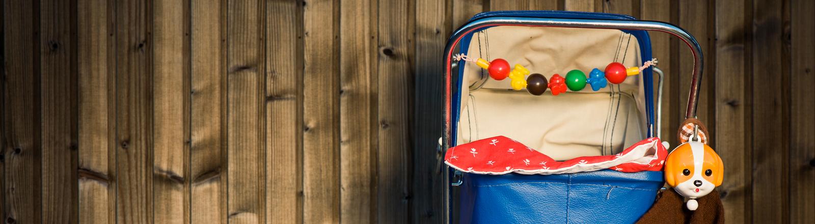 Ein leerer Kinderwagen vor einer Holzwand