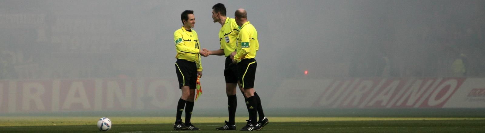 Schiedsrichter, umzingelt von Fußballspielern, zieht eine gelbe Karte