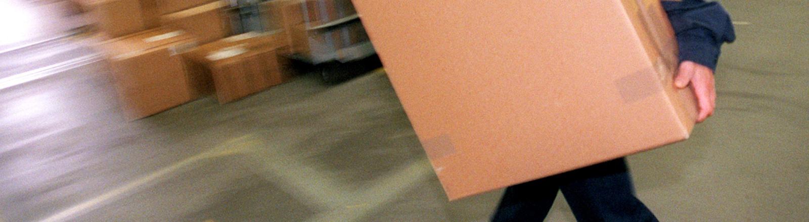 Paketbote, von dem man fast nichts sieht, weil er ein großes Paket trägt