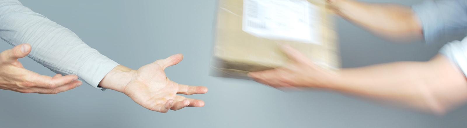 Zwei Hände, die ein Paket an zwei andere Hände weiterreichen