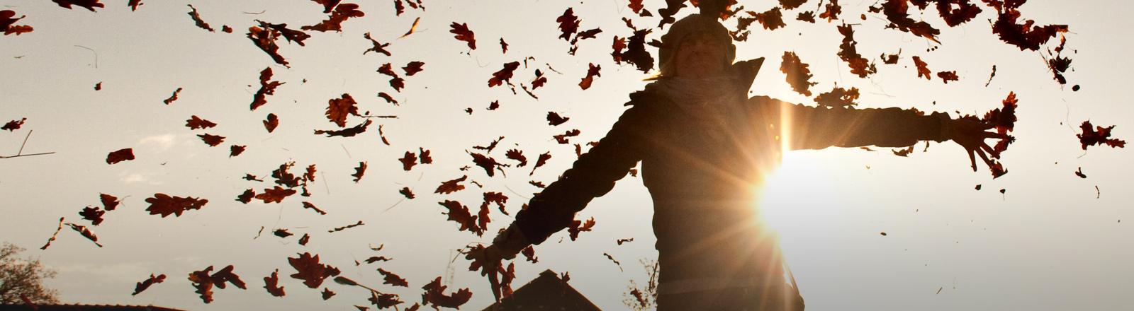 Eine Frau tanzt in wehenden Blättern in der Sonne.