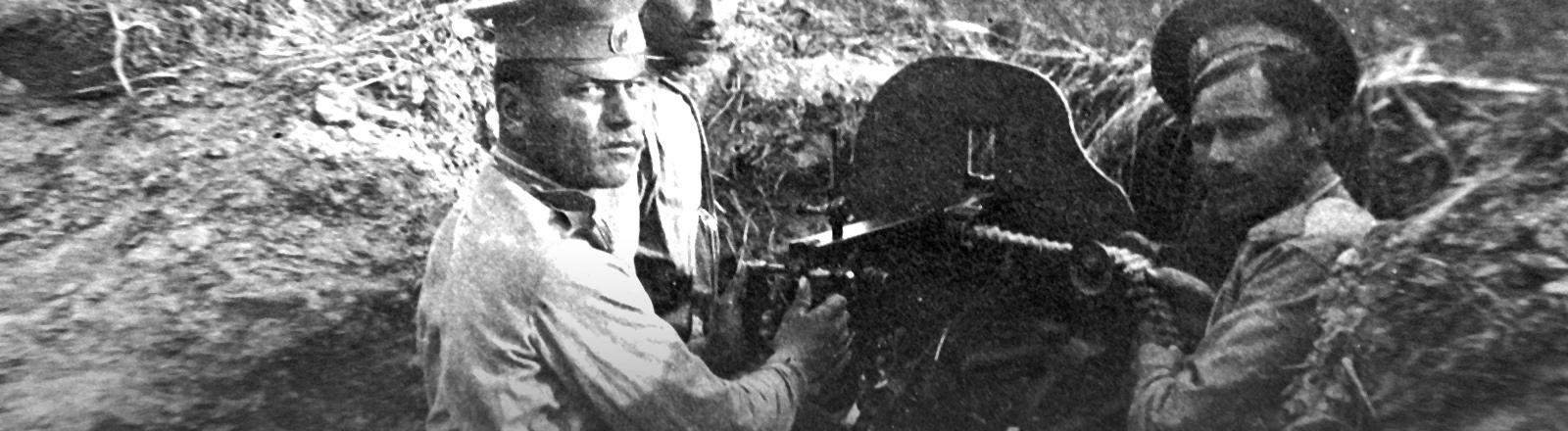 Drei Soldaten an einem Maschinengewehr im ersten Weltkrieg.
