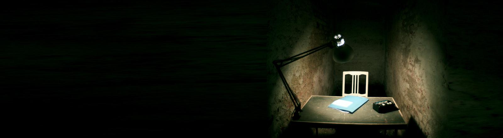 Ein Schreibtisch in einem kleinen, dunklen Raum.