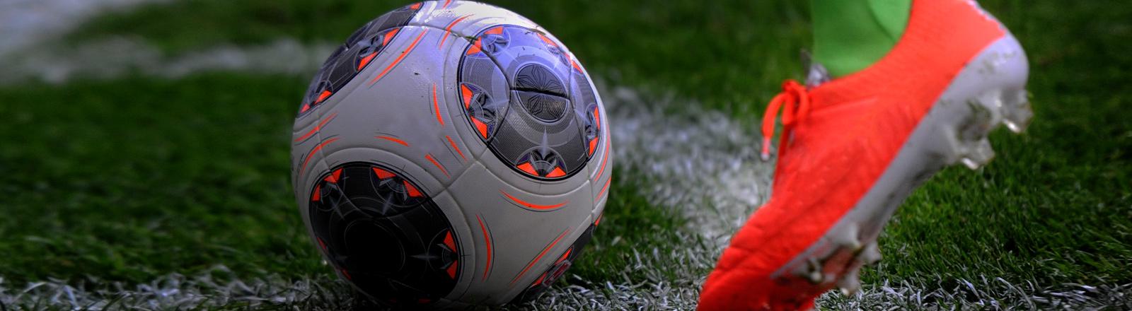 Ein Bein mit einem orange-farbenen Fußballschuh tritt gegen einen Fußball.