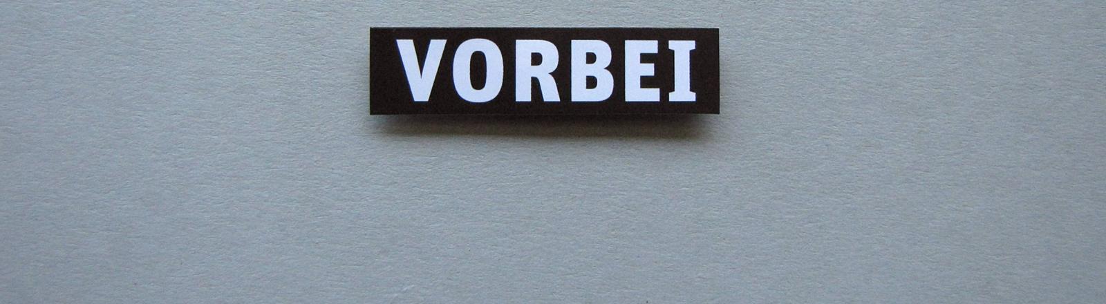 """Graue Wand, an der ein Schild hängt, auf dem """"vorbei"""" steht."""