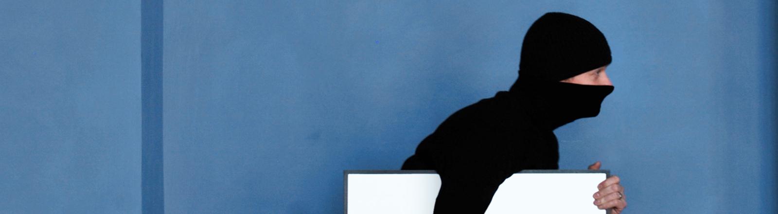 Schwarz gekleideter Mann mit Sturmmaske und einem weißen viereckigen Paket unterm Arm.