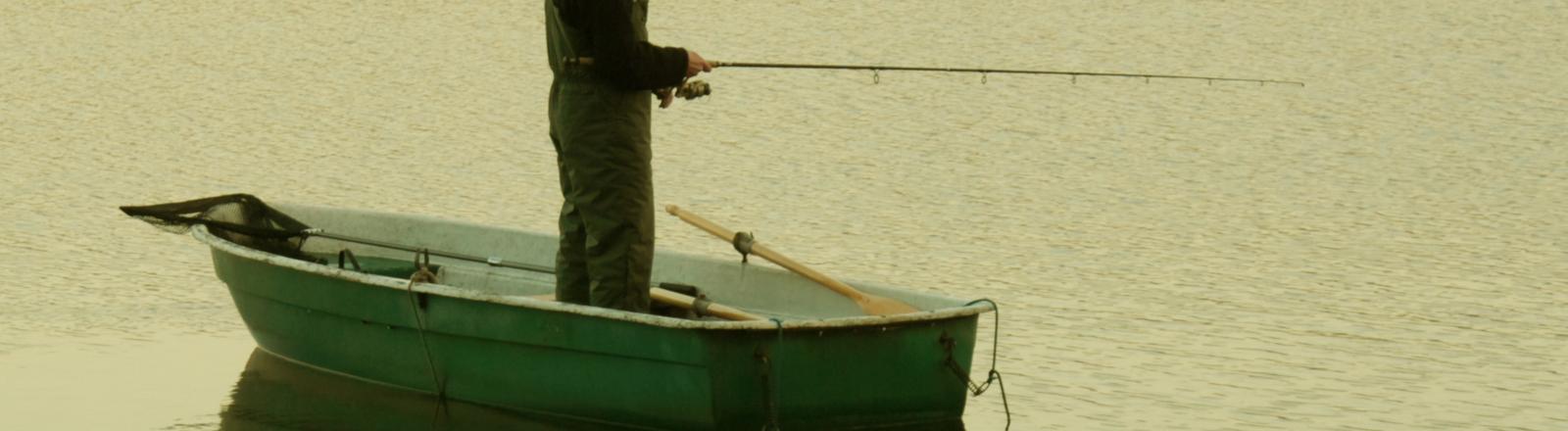 Fischer auf Boot mit Angel