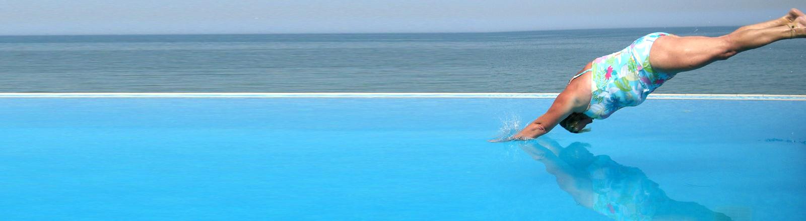 Eine Frau springt in einen Pool.