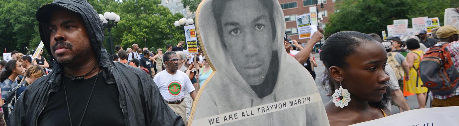Ein Mann hält eine Pappfigur von Trayvon Martin vor sich.