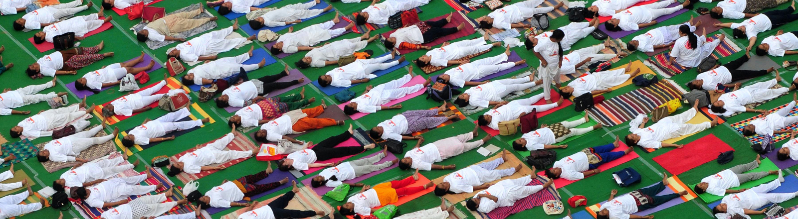 Viele Menschen, die auf einer Yogamatte liegen.
