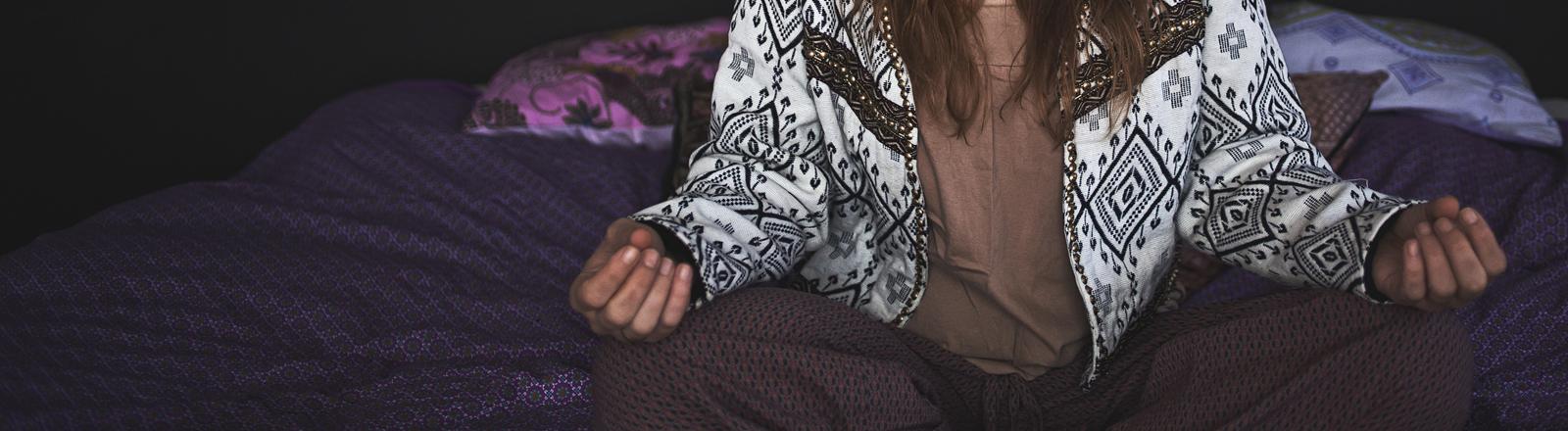 Frau meditiert im Schneidersitz.