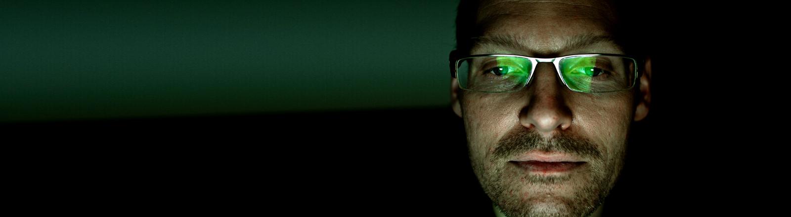 Ein Mann mit Brille guckt auf einen Monitor.