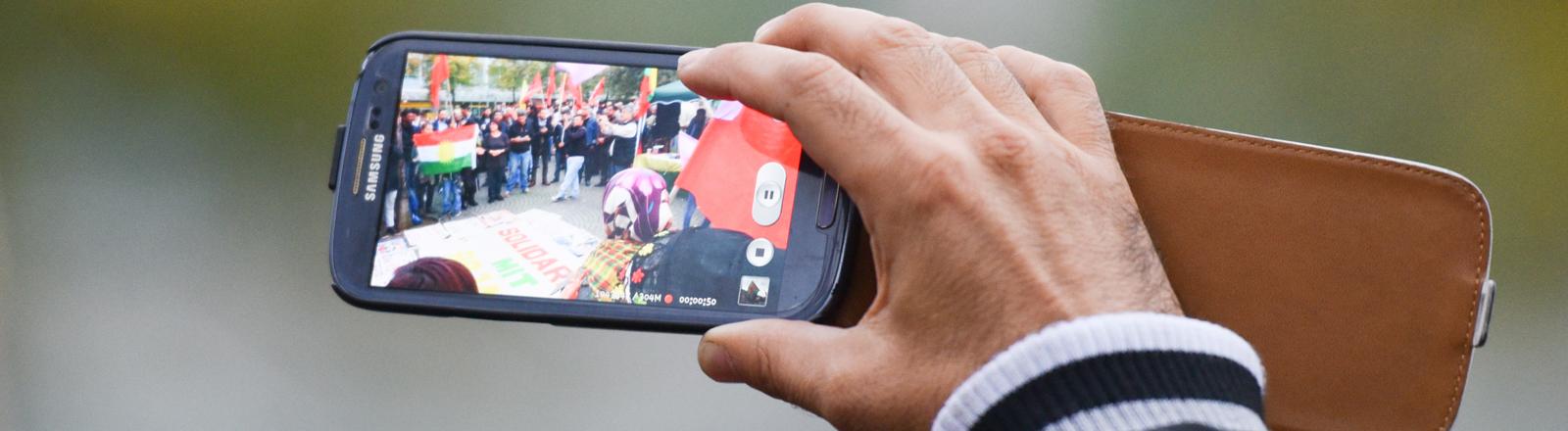 Jemand filmt eine Kurden-Demo mit dem Smartphone.