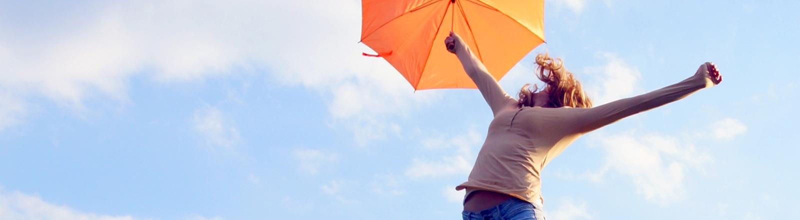 Eine Frau springt auf einer Wiese vor blauem Himmel in die Luft.