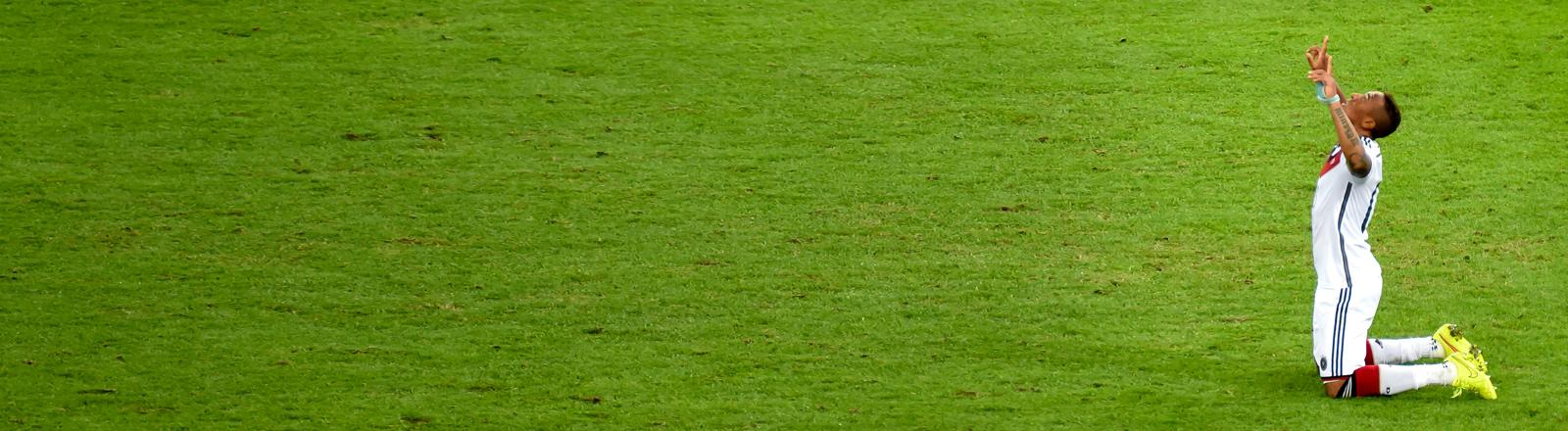 Fußballer Jerome Boateng kniet nach dem WM-Finale 2014 auf dem Rasen.