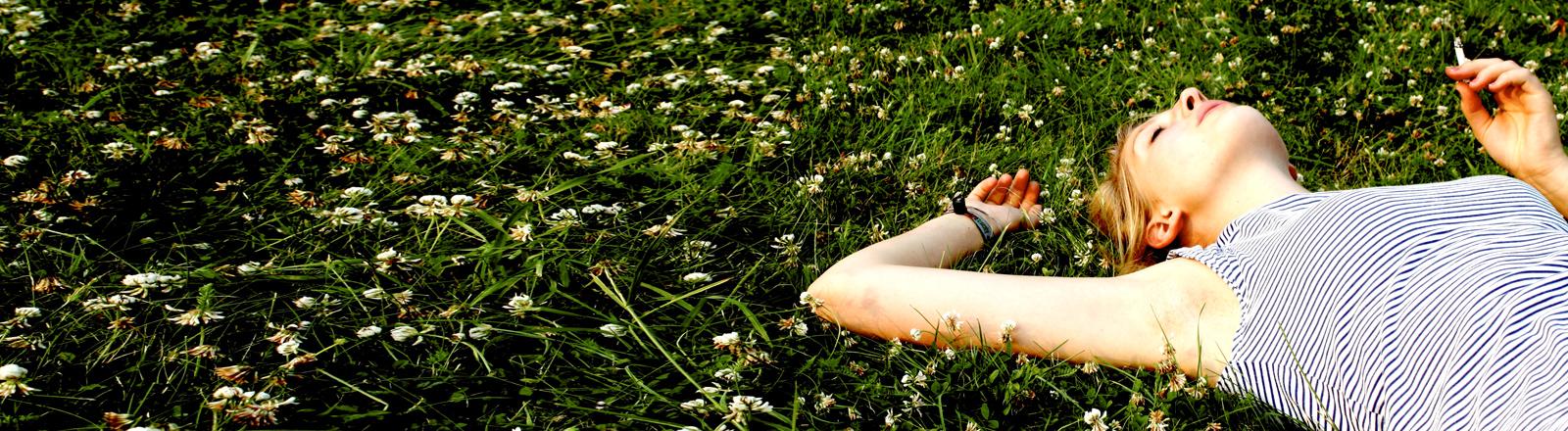 Eine junge Frau liegt rauchend auf einer Wiese.