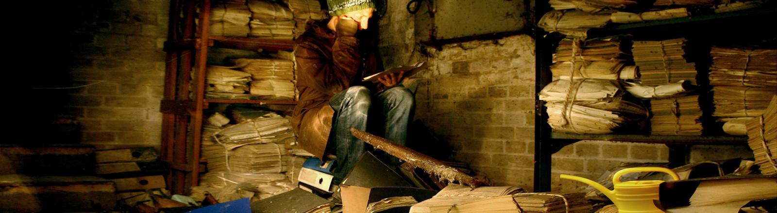 Eine Person sitzt auf einem Haufen Akten und Ordnern in einem dunklen Raum.