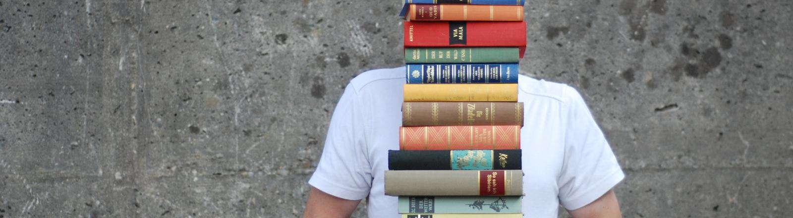 Mensch, der einen Bücherstapel trägt.