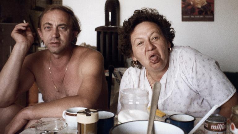 Ältere Dame neben einem Mann am Tisch. Sie streckt die Zunge heraus.
