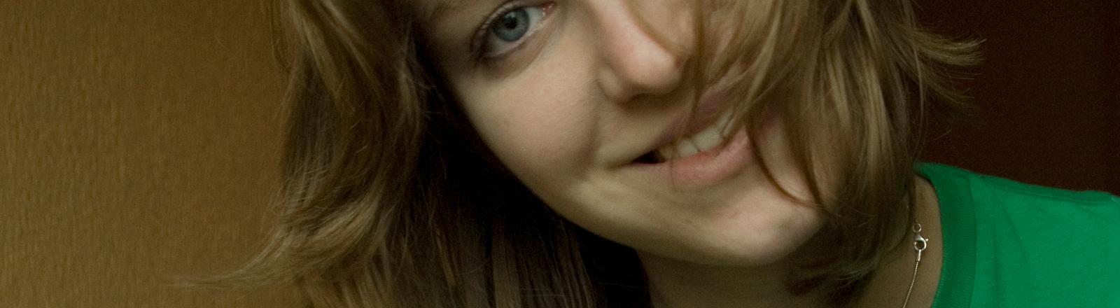 Eine nett lächelnde Frau legt ihren Kopf zur Seite.
