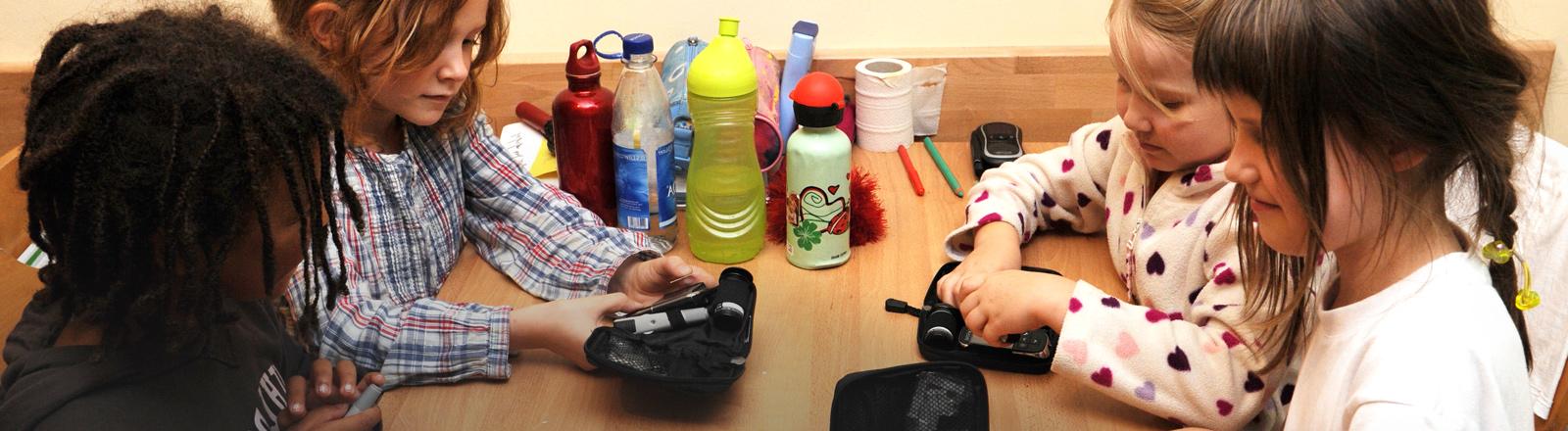 Kinder mit Diabetes sitzen gemeinsam Tisch vor ihren Blutzuckermessgeräten.