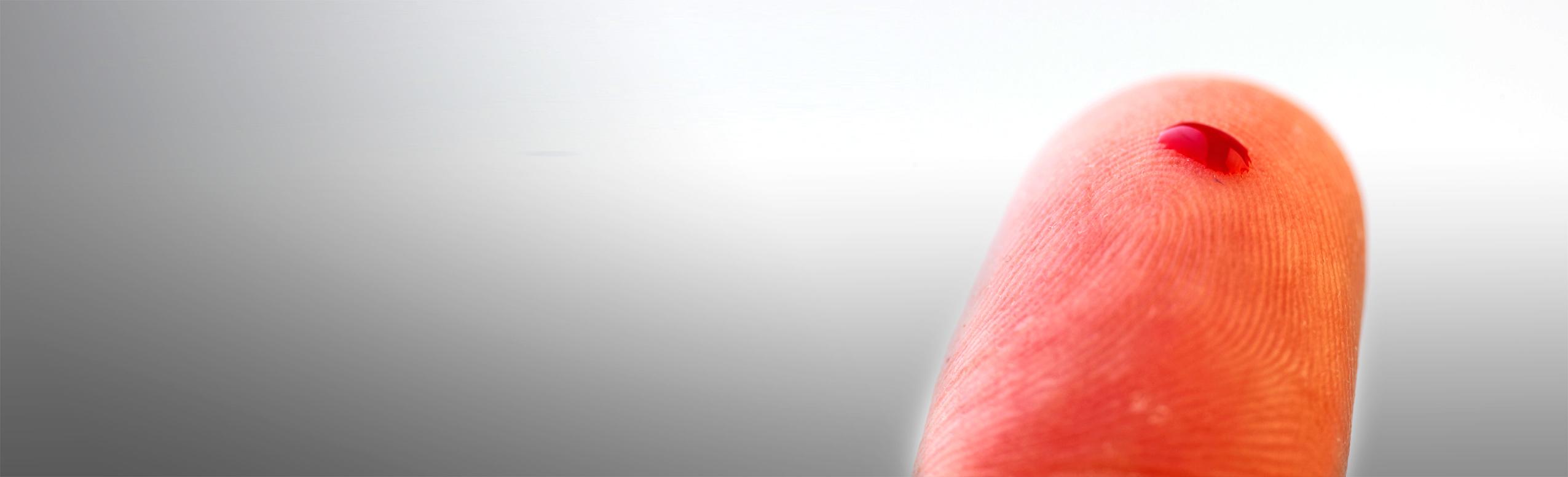 Ein Tropfen Blut auf einem Finger.