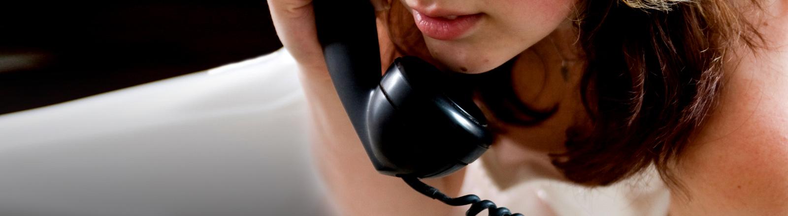 Eine Frau hält einen Telefonhörer in der Hand.