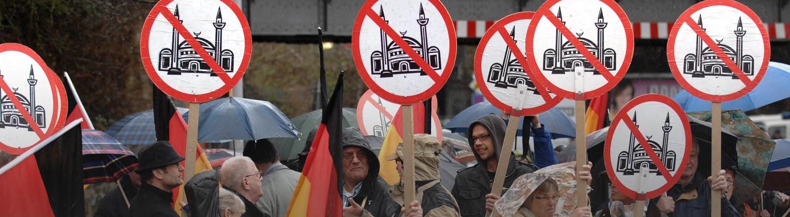 Menschen halten Schilder hoch und demonstrieren damit gegen Moscheen