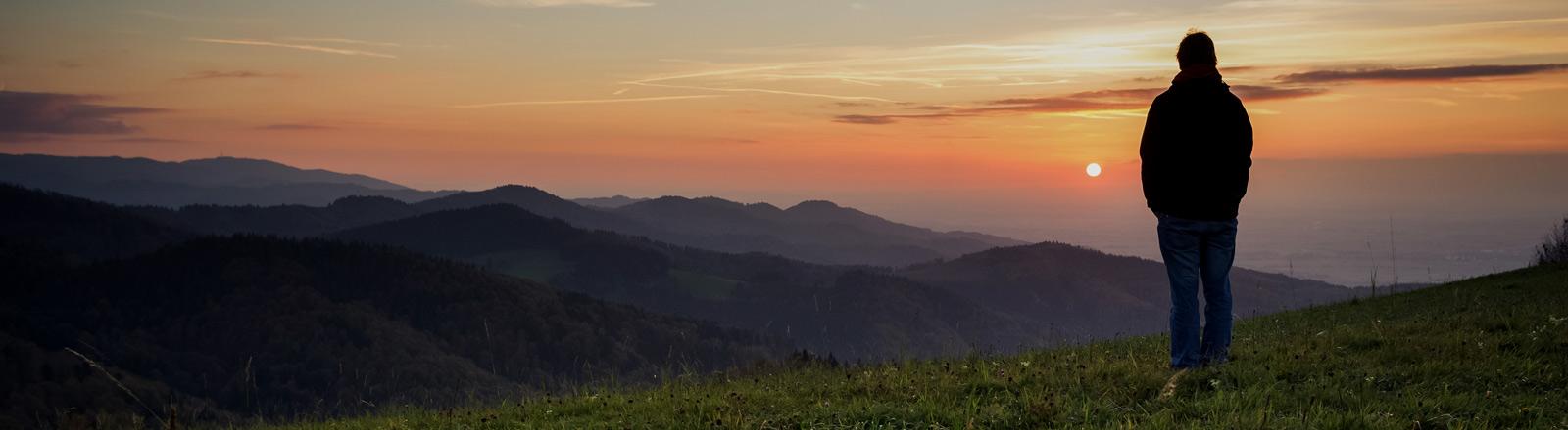 Ein Mann steht auf einem Berg und guckt in den Abendhimmel.