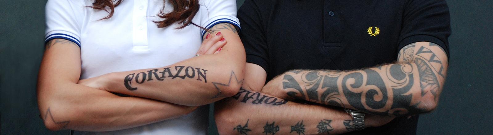 Eine Frau und ein Mann mit verschränkten Armen vor der Brust