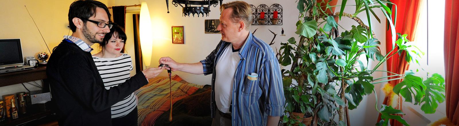 Eine über die Plattform Airbnb vermittelte Wohnung wird übergeben. Der Vermieter überreicht den Mietern den Schlüssel.