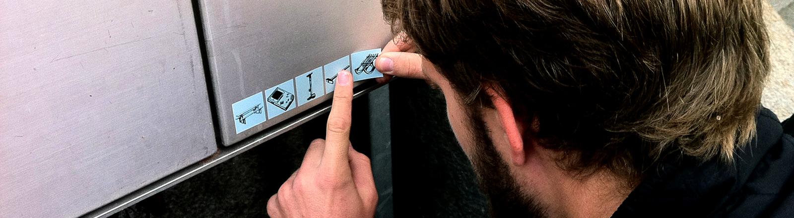 Eine Person klebt Sticker mit Gegenständen auf einen Briefkasten.