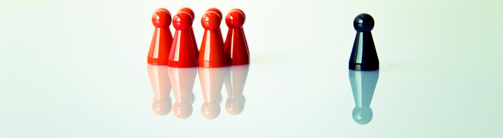 Sechs rote Spielfiguren und eine schwarze.